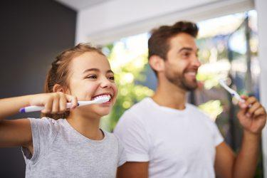 Young girl showing father how to brush their teeth - Riley Dental Group